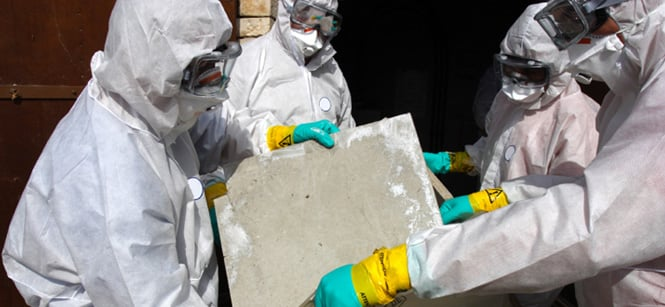 People in white suits carrying panels with asbestos